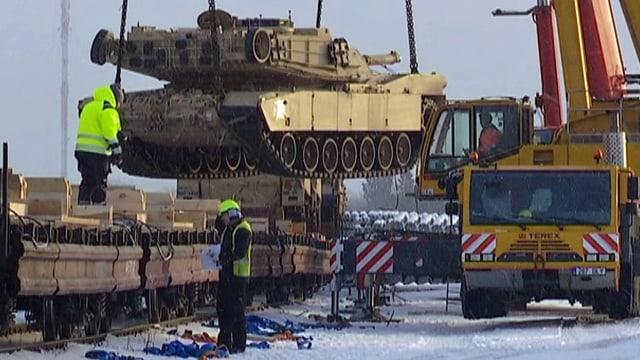 Ein Panzer wird mit einem mobilen Kranwagen von einem Eisenbahnwagen abgeladen.