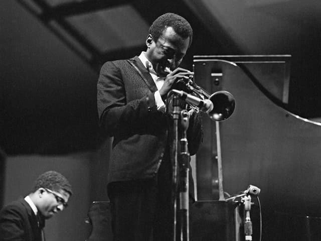 Schwarzweissbild: Davis mit Trompete auf einer Bühne, im Hintergrund Hancock am Klavier.
