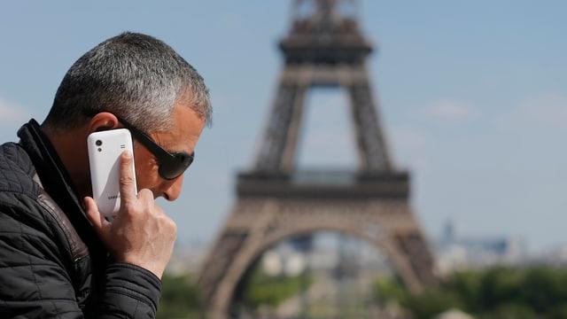 Ein Mann telefoniert mit dem Handy vor dem Eiffelturm in Paris.