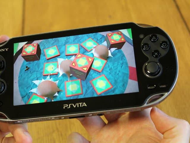 Bild einer Playstation Vita auf der im Spiel «Tearaway» die Fingerspitzen des Spielers durch die Rückwand des Geräts ins Spiel hineinzuragen scheinen