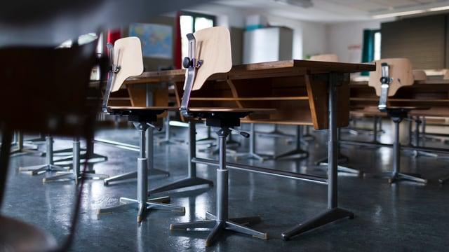 Leeres Schulzimmer mit Pulten und Stühlen.