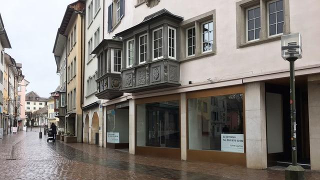 Altstadthaus mit leeren Schaufenstern und Gasse