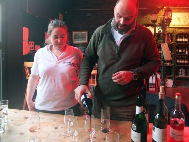 Ein frau und ein Mann stehen an einem Tisch. Er schenkt ein Glas Rotwein ein, auf dem Tisch stehen drei weitere Weinflaschen