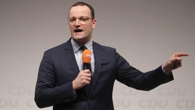 Jens Spahn mit Mikrofon in der Hand.