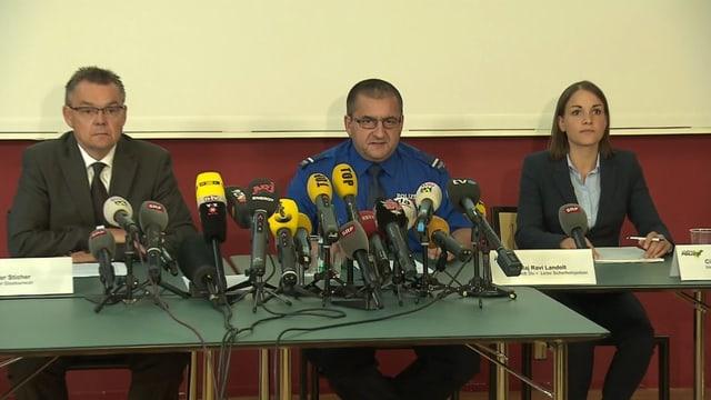 Podium der Medienkonferenz mit drei Personen.