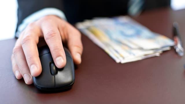 Ein Mann mit einer Computermaus in der Hand sitzt an einem Tisch, auf dem einige Hunderternoten liegen.