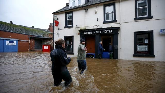 Eine Frau und ein Mann gehen durch eine überschwemmte Strasse.