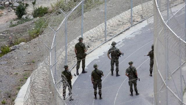 Spanische Soldaten patrouillieren am  doppelt gesicherten Grenzzaum zur Enklave Ceuta