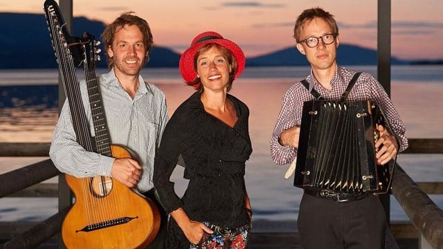 Drei Musiker vor einem Gewässer.