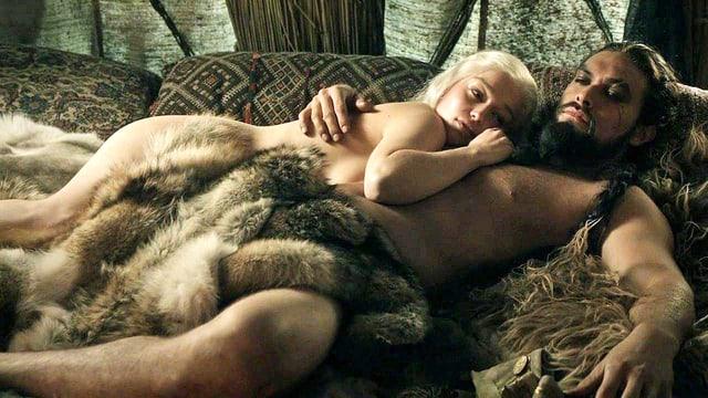 Ein Mann und eine Frau, beide nackt, liegen Arm in Arm auf dem Bett.