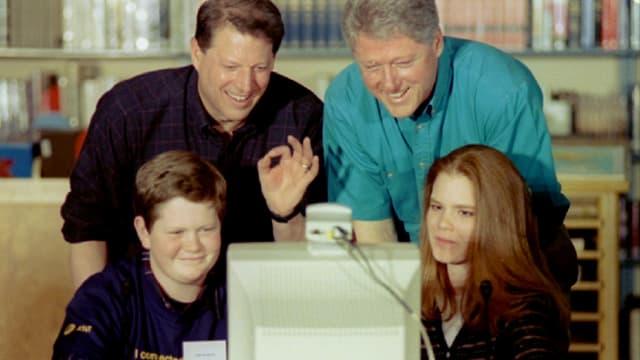 Zwei Männer stehen hinter zwei Schülern, welche an einem Computer sitzen.