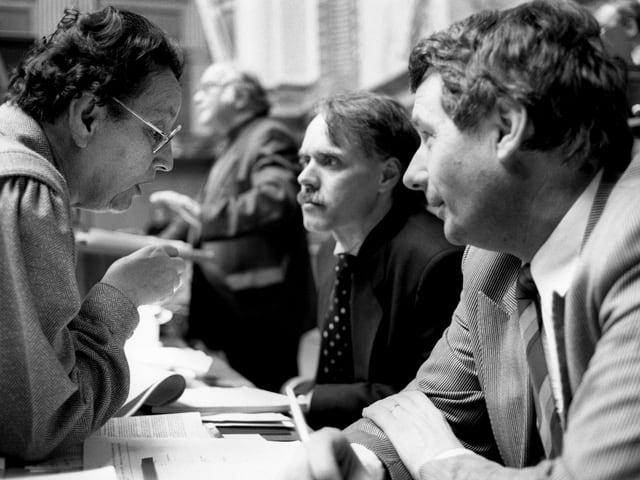 Auf einer schwarz-weissen Fotografie sieht man drei Personen, die miteinander diskutieren.