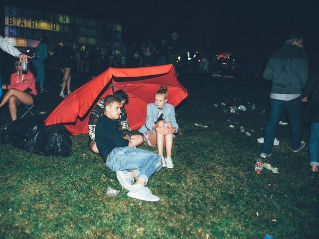 Festivalbesucher unter einem roten Sonnenschirm
