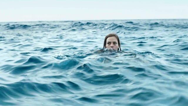 Ein junges Mädchen im Meer. Man sieht nur ihren Kopf aus dem Waser ragen.