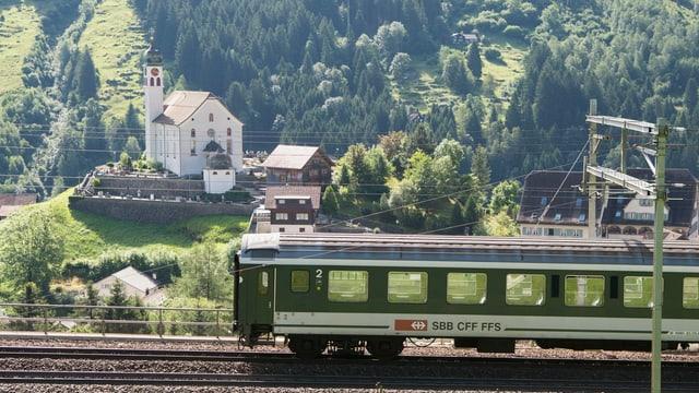 Zug fährt an Kirche vorbei.