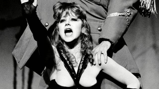 Frau auf Theaterbühne in erotischem Kostüm.