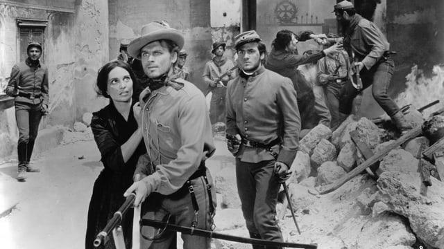 In den engen Strassen einer Stadt, im Hintergrund Männer in Uniform und mit Gewehren. Im Vordergrund ein Mann mit Gewehr in der Hand, eine Frau hält ihn an der Schulter.