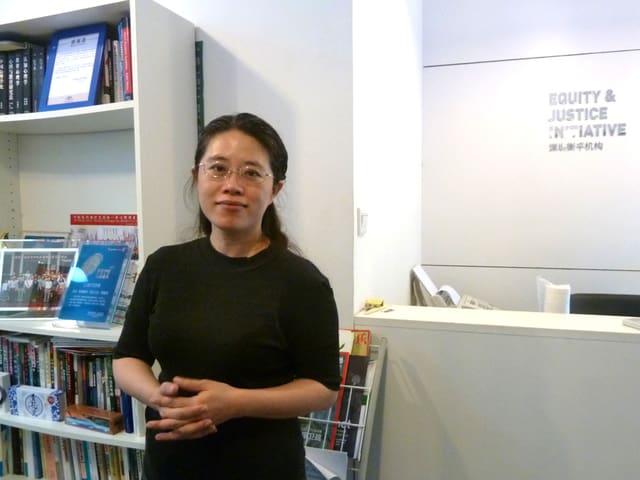 Eine junge Frau steht in einem weissen Büro, im Hintergrund steht ein Bücherregal.