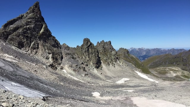 Blick in eine steinige Berglandschaft. Im Vordergrund kleinere Eisfelder