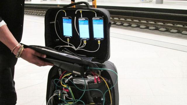 In einem Koffer stecken drei Handys, die mit Kabeln mit Messtechnik verbunden sind.
