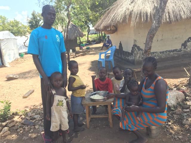Ein Südsudanese steht neben seiner Familie, die Hände auf den Schultern eines Kleinkindes. Daneben sitzen seine Frau und die fünf anderen Kinder rund um einen Tisch und essen aus derselben Schüssel.