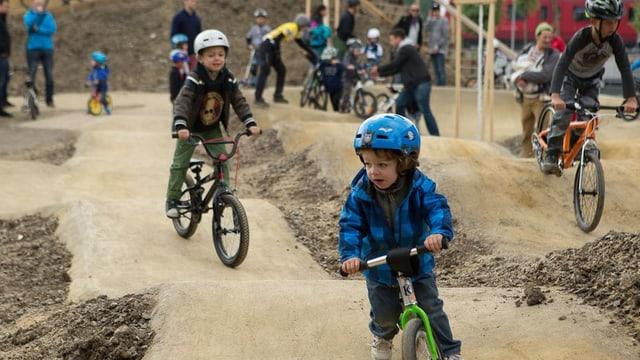 Kinder, die in einem Bikepark umherfahren.