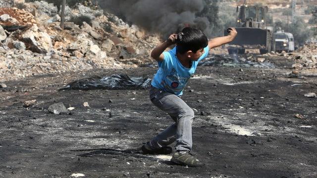 Ein Junge wirft einen Stein.
