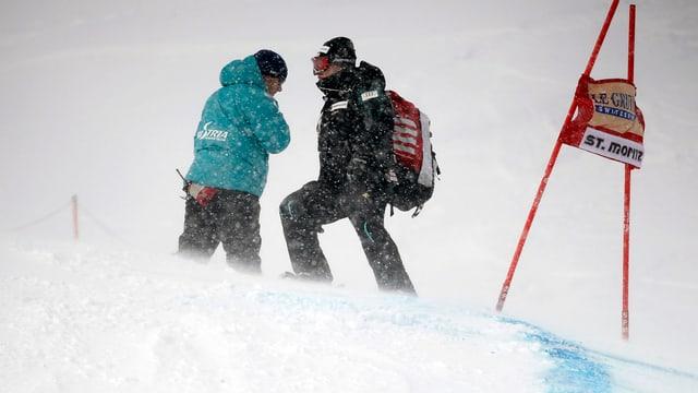 Zwei Trainer im Schneetreiben.