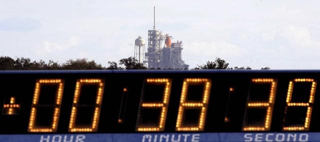 Archivbild einer Countdown-Anzeige vor einem bereit stehenen Space Shuttle im amerikanischen Bundesstatt Florida.
