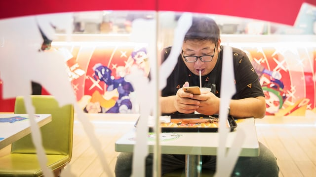 Ein Mann sitzt in einem Fast-Food-Laden und schaut auf sein Smartphone.