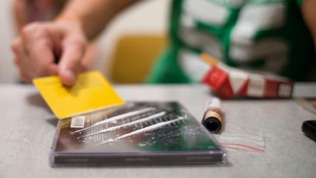Ein Kokainkonsument teilt die Droge mit einer Karte in dei Linien.