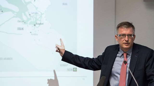 Markus Seiler, Direktor des NDB, an einem Rednerpult. Er zeigt mit dem Finger auf eine Karte hinter ihm.