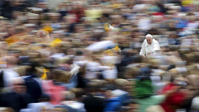 Papst Franziskus in Weiss in einer Menschenmenge, er ist auf dem Foto als einziger in der Menge scharfgestellt.