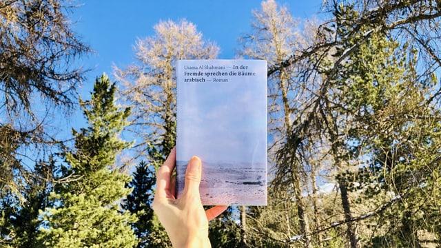 Annette König hält den Roman «In der Fremde sprechen die Bäume arabisch» von Usama Al Shahmani vor Nadelbäume