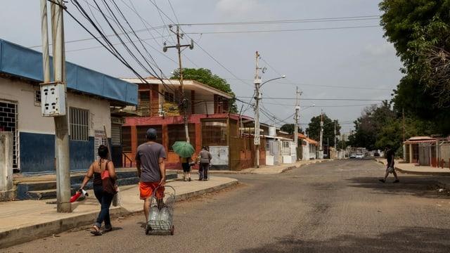 Menschen tragen ihre Wasserkanister zu Fuss durch die Stadt.