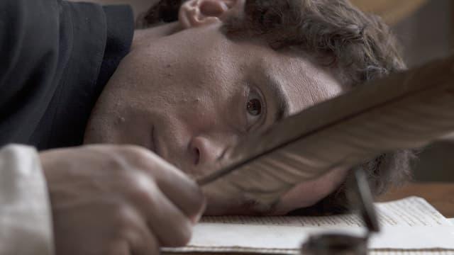 Ein Schriftsteller mit dem Kopf auf seinen Schriften betrachtet die Feder in seiner Hand.