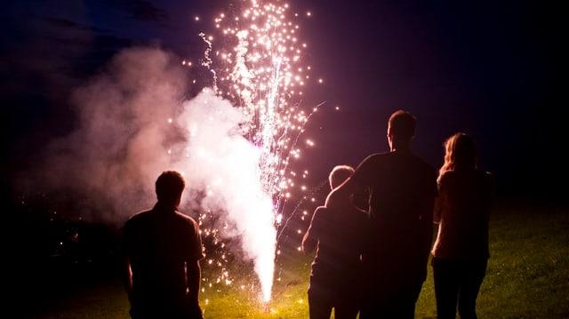Ein Vulkan spuckt Feuer, vier Zuschauer stehen davor und geniessen den Anblick