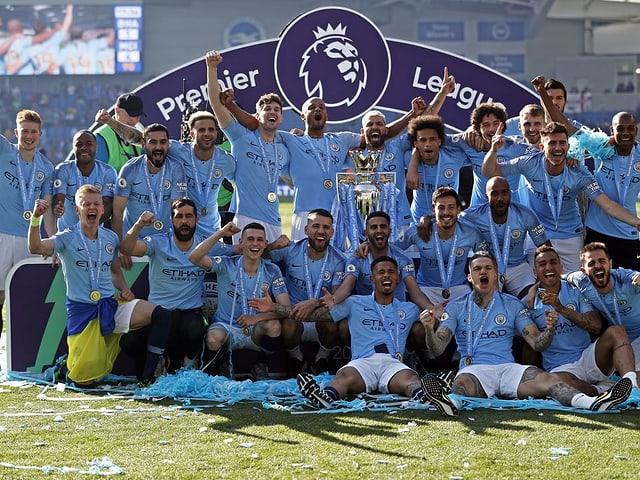 Die Spieler von Manchester City feiern mit der Trophäe.