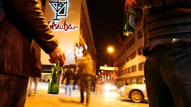 Dus umens cun ina buttiglia da biera sin las vias da Cuira davant la Felsenbar.