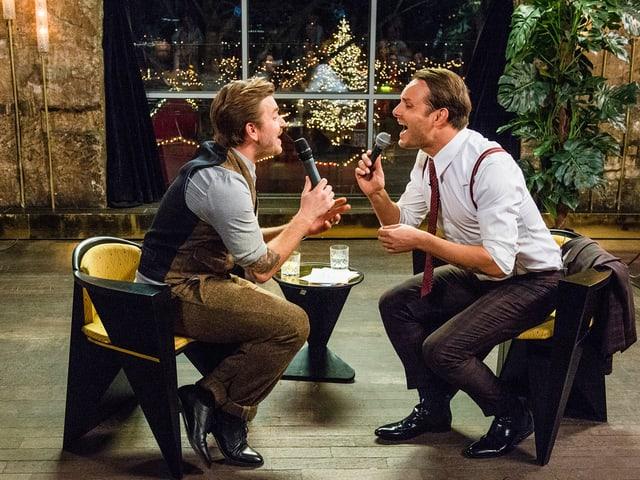 Baschi und Deville sitzen sich gegenüber, halten ein Mikrofon in der Hand und singen ein Duett