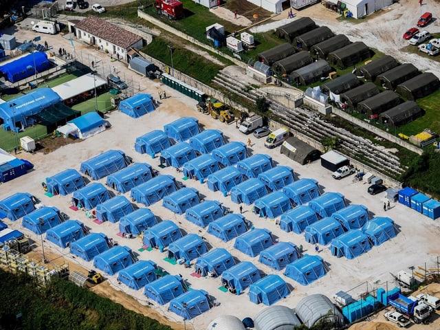 Luftaufnahme: Blaue Zelte in Reih und Glied auf einem Platz.