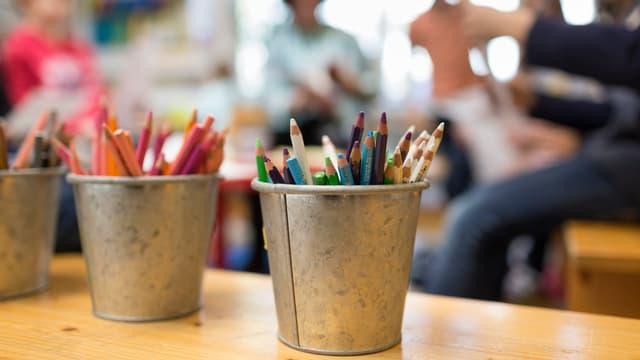 Blechdosen mit Malstiften und im Hintegrund eine Schulklasse.