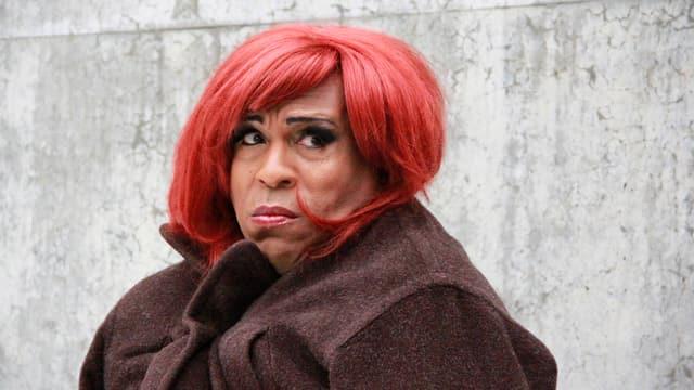 Ein Mann als Frau mit rotem Haar.