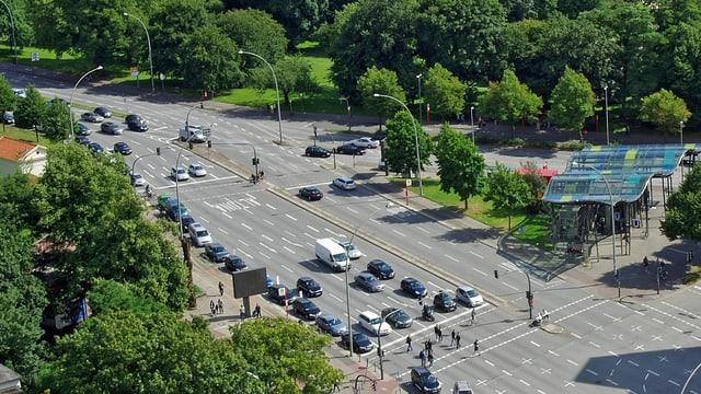 Eine mehrspurige Kreuzung, umgeben von Bäumen und Grünflächen in der Stadt Hamburg.