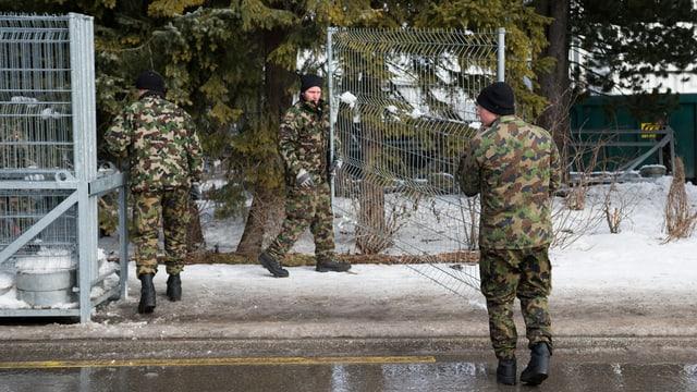 Armeeangehörige tragen einen Zaun.