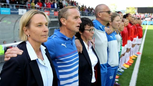 Martina Voss-Tecklenburg und der Staff aufgereiht beim Abspielen der Nationalhymne.