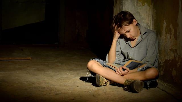 Kind sitzt in dunklem Keller und liest