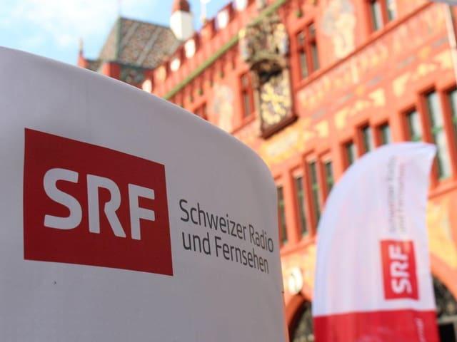SRF Logo, im Hintergrund das Rathaus