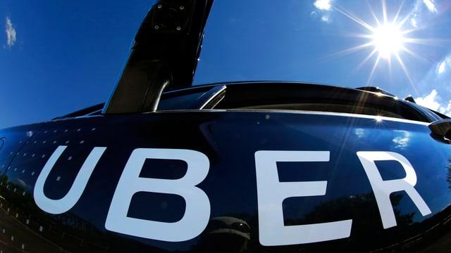 """Aufschrift """"Uber"""" am Heck eines Autos, im Hintergrund am Himmel die Sonne."""