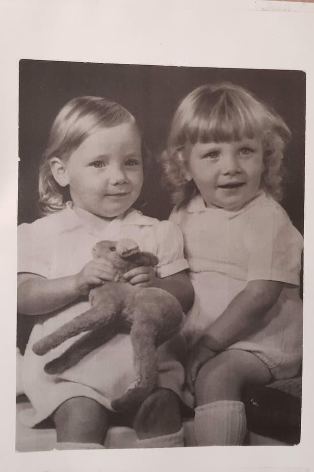 Zwei kleine Zwillinge auf einem Schwarz-Weiss-Foto mit einem Stofftier in der Hand.